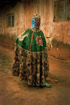 It is a man - a masquerader from Benin who attends Yoruba funerals to guide the passage of the deceased to the spirit world.via Saatchi