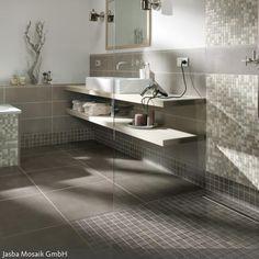 Ein wenig maskulin wirken die grauen Fliesen der Badezimmergestaltung. Die dunklen Wand- und Bodenfliesen werden hierbei leicht spielerisch von den Mosaikfliesen…