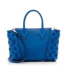 An iconic Louis Vuitton bag in blue lagon Veau Cachemire leather with calfskin trim and palladium brass hardware. Details include Monogram tufted sides, two rolled handles, a magnetic snap closure, and alcantara lined interior with two open and one zip pocket. This mini bag can be carried by the top handles, over the shoulder, or cross body.