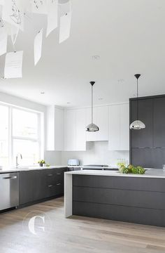 Modern black and white kitchen features white flat front upper cabinets and black flat front bottom cabinets paired with white quartz countertops and a glossy white grid tile backsplash.