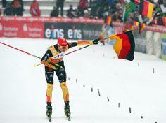 Eric Frenzel läuft mit der deutschen Fahne in der Hand beim Weltcup der nordischen Kombinierer in Klingenthal als Sieger über die Ziellinie und verneigt sich dabei.    Der deutsche Sportler holt in der Vogtland Arena seinen vierten Einzelsieg in Serie. Damit sind bei den vergangenen sechs Wettbewerben nur DSV-Kombinierer ganz vorn gewesen. (Foto: Hendrik Schmidt/dpa)