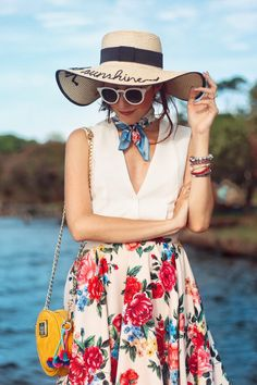 Summertime outfit with a feminine and vintage inspired outfit wearing a gorgeous floral midi skirt, a nice hat and pompom sandals.