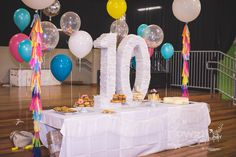 Owens 10th birthday  dessert table cake table Giant balloons, confetti balloons, teal, yellow, silver, brights. Funfetti confetti theme with lots of bright white and a nice fun vibe.