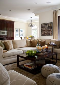 Large beige sectional with brown and green accent pillows. Creamy neutral walls with tonal silk draperies. Contemporary wood console table on top of a more traditional rug with fun pouf seating.