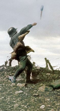 A German soldier - with the iconic green uniform clearly visible - throwing a grenade over the barbed wire protecting the British trenches