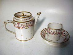 PARIS. Une tasse litron et sa sous-tasse et une théière couverte en porcelaine émaillée blanc à décor polychrome de rinceaux et de fleurs. Avec rehaut d'or. Début XIXème siècle. Hauteur théière : 12 cm. Usures, égrenure au bec verseur.