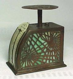 The Front has a Postage Scale label with its weight measures and rates in the front. It is marked Crescent Postal Scale and has a date of January 31st 1899 in the lower right hand corner. There is some earlier dates to the left but this is the latest one. The mechanism was made by Crescent but the Acid Etched Pattern and metal along with the Patina was done by Tiffany Studios.