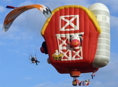 A motor paragliding expert approaches a hot air balloon taking flight at the Philippine Hot Air Balloon Fiesta - photo by Rolex Dela Pena; at Clarkfield, Pampanga Province, north of Manila, Philippines, 2011 Air Balloon Rides, Hot Air Balloon, Albuquerque Balloon Festival, Photo New, Balloon Pictures, Balloon Flights, Air Ballon, Paragliding, Helium Balloons