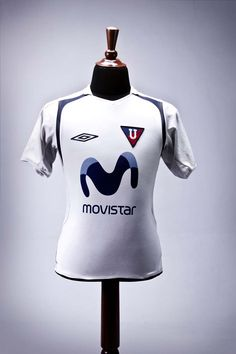 """Umbro designed a minimalist jersey with refined blue lines for the so-called """"Plantilla Mundialista"""". The era of big names was formed in 2006: Christian Mora, goalkeeper from the World Cup, Neicer Reasco, Paul Ambrosi, Giovanny Espinoza, Patricio Urrutia, Édison Méndez and the historic scorer of the Ecuadorian team, Agustin Delgado. They came together with the Paraguayan internationals Carlos Espínola and Enrique Vera and with the prominent Roberto Palacios of Peru. Despite some historical…"""