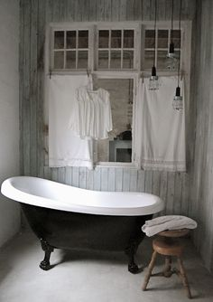 love the big mirror on the wall with the vintage window frames over top. Also, the towel racks and the hanging lights.