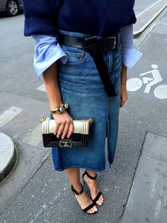 denim pencil skirt at a mid-length with a mini clutch and a men's belt