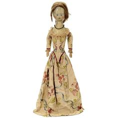 <B> George III Wooden Doll, c. 1810 </b> <br> English, with carved and painted head, inset blue enamel eyes, brown hair wig, flat-backed torso with pinned cloth upper arms, carved wood hands, pine upper legs with mortice joints at hips and knees, painted lower legs and silk brocade costume, height 28 in. (71 cm), head overpainted, missing finger tips and part of left foot. <br> <br> <B> Frühe englische Holzpuppe, um 1810 </b> <br> Geschnitzter und bemalter Kopf, eingesetzte Augen, blau/weiß…
