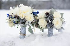 Gorgeous winter wedding bouquets with white roses, silver brunia berries, pinecones and delphinium