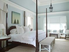 light blue walls with white bedding and dark bed frame and furniture