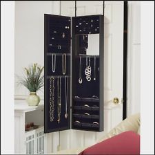 Over-the-door jewelry armoire and mirror. When closed, the cabinet is a long mirror housed in a smart black frame. When opened, the cabinet reveals ample storage to keep your items organized with specific spots for necklaces, bracelets, earrings and rings. Jewlery Organizer Storage.   In Stock: $137.95
