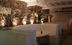 Stone wall behind booth seating with lovely accent lighting/ BAR Booth Seating, Accent Lighting, Take A Seat, Open Plan, Restaurant Bar, Future House, This Is Us, Paella Party, Antiqued Mirror