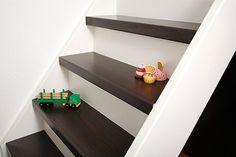 Mooie witte trap met donker houten treden voor in de gang