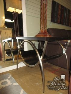 "Glass top end table on a curved dark wood and silver base. Love the curved base and modern style legs. 28""wide x 23""deep x 25""high. At posting, we have the matching coffee table."