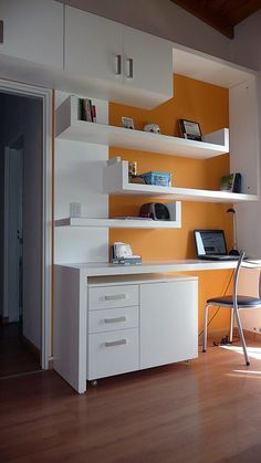 Modern Home office white desk floating shelves orange wall behind