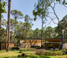 Three individual structures make up the larger house nestled in forest