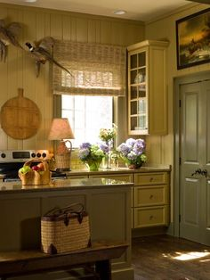 Colorful Kitchens with Charisma - Traditional Home®.   I LOVE the colors here.  It could seem dark, but the island reflects light.  Very clever.  And look how the upper cabinet door faces the window?  I NEVER would have thought to do that!  Smart. I can't stop studying the elements of this kitchen.
