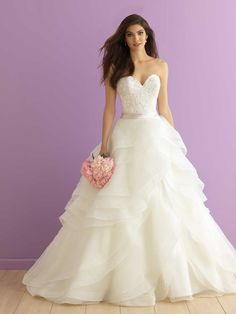 Designed to mimic rose petals, the ruffles of this strapless sweetheart ballgown bridal gown's full organza skirt unfold gracefully from the satin waistband.