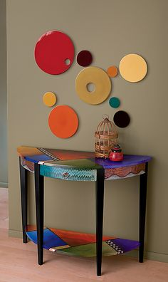 All the Colors at Once by Wendy Grossman. This table is a half moon shape with a shelf on the bottom. It is made from a hard wood, called Poplar. The paint is all acrylic as is the varnish. Each table gets a minimum of 10 coats of water based varnish. The table is water resistant, but we recommend coasters for drinks. The table is embellished with embossed copper and complimented with real gold, silver and copper leaf. Available at www.artfulhome.com