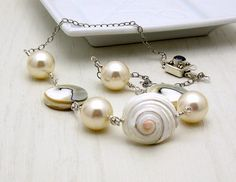 $139 ...white shell and pearl necklace with sterling silver accents. I have been saving these shell pieces, purchased in Amsterdam, for years ...why? Who knows. But if you are looking for a statement piece to take on your next cruise ... or just to wear to the office to perk up an outfit ...or to a small romantic cabaret...you've just found your next best friend.    I chose to use Swarovski glass pearls because ... well, that are...
