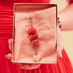 Give your cocktail some love with this adorable garnish. Roll cranberries in sugar, thread through a metal skewer. Create a fondant heart for the arrow tip and your drink's complete.