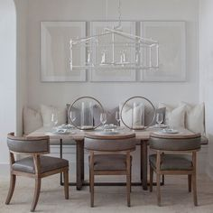 A gray dining room with leather barrel chairs, a white lacquered bamboo chandelier and a white-washed dining room table.