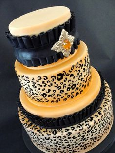"Fabulous handpainted leopard print wedding cake with decorative ruffles of modeling chocolate and top tier adorned with an ornate ""jewel"" made of poured sugar. Created by designer Julie Hill, owner of Layers in Salt Lake City, Utah...."