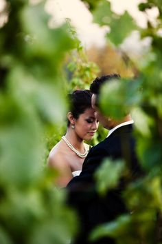 A bride a groom have a quiet moment in the vineyard before their wedding.  Image by Atelier Pictures.