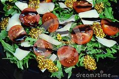 Delicious refreshing salad of arugula, cherry tomatoes and Gouda cheese with balsamic sauce, French mustard. Close-up dishes.