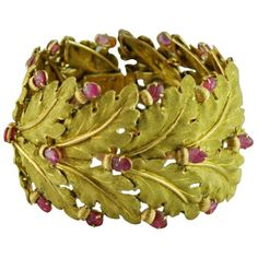 Gold & Carved Ruby Bracelet by Buccellati / Italy / circa 1960s /   Wide yellow gold cuff bracelet designed as a series of textured oak leaves with carved ruby acorns