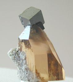 Bixbyite, (Mn+++,Fe+++)2O3, Topaz, Maynard's claim, Thomas Range, Juab Co., Utah, USA. Dimensions: 24 x 15 x 7 mm. Bixbyite crystal perched on a gemmy topaz crystal. Copyright: © D. Richerson