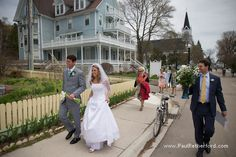 Walking to your wedding reception from Ste Anne Church on Mackinac Island, Michigan to the reception at the Island House Hotel photo by Paul Retherford Wedding Photography and flowers by St. Ignace Greenhouse #mackinacwedding #mackinacislandwedding #puremichigan #northernmichigan #mackinacisland #weddingidea #weddinglocation #destinationwedding #weddinginspiration #weddingday #wedding #Canon #candid