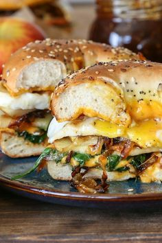Scrumptious fall-inspired grilled cheese bagel sandwich with sliced apple, pear, cheddar cheese, caramelized onions, arugula, and sunny-side up egg – a melt-in-your-mouth experience for any m…