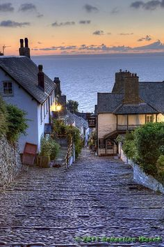 Clovelly, England.  The cobbled, traffic-free, high street, built into a cleft in a 400' high cliff, tumbles its way down past whitewashed cottages festooned with flowers to the tiny working port.