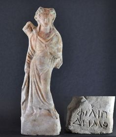 Greek terracotta statuette of female, 3rd century B.C. Hellenistic period terracotta figurine of female wearing himation, arm raised, inscribed with maker's name on back, ramains green and red polychromy, 26 cm high. Private collection