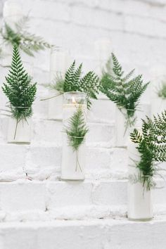 White glass enclosed candles with ferns - a nice way to add a touch of greenery and light.