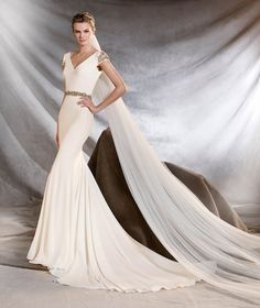 Orville is a mermaid wedding dress with a v neck. See more of this style now by visiting Pronovias.