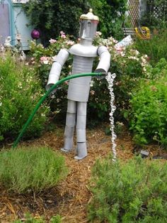 Yard Art, head is made from a coffee pot and body made with food cans.
