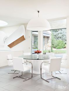 FontanaArte's Avico pendant hangs above a custom-fabricated table paired with Swaim chairs from Hoff Miller in the breakfast area. Charles Wooldridge sculptures line the wall above a spiral staircase that leads downstairs.