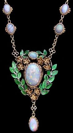 JOHN PAUL COOPER (1869-1933) (Attrib.) An Arts & Crafts gold necklace. The central opal pendant set within a mount of green enamelled leaves suspended from a chain with cabochon opals and green enamel and flower links. English, circa 1910. #opalsaustralia