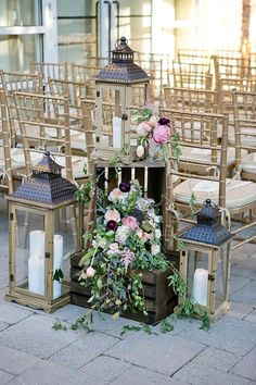 Arrangements of wooden lanterns with candles and wooden crates overflowing with greens, white, pink and blush roses marked the entryway to the ceremony at Stone House at Stirling Ridge in Warren, New Jersey. Wedding Aisle Decorations, Wedding Lanterns, Lanterns Decor, Wedding Flower Arrangements, Wedding Centerpieces, Floral Arrangements, Wooden Lanterns, Candle Arrangements, Graduation Decorations