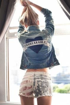 "Adding a feminine and playful touch to your denim jacket. Vintage wash denim jacket featuring heart shadow patch with embroidered phrase ""Unbreakable"" on back."