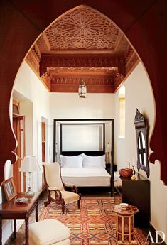 A Berber carpet echoes the geometric ceiling of a bedroom in a Moroccan home.