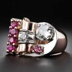 This Streamlined Moderne.- circa 1940s - Retro ring highlights a bright and shining three-quarter carat European-cut diamond embraced by a white gold crescent at the end of this artistically conceived, half-asymmetrical jewel. Crafted in radiant rose gold and rubies with contrasting white gold accents. Sleek and chic