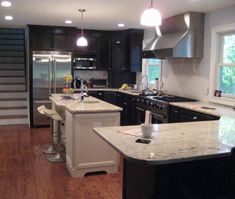 This transitional U-shaped kitchen uses subtle grey & white modern wall finishes to accent the dark cabinetry.