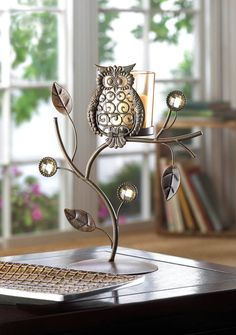 """#14604 Wise Owl Votive Stand With its fanciful theme and its rich, earthy colors, this vine shaped candle stand is a wise decorating choice indeed! Cute owl ornament is ever so enchanting when backlit by a candle's glow. Item Weight: 0.6 lb.  7 1/4"""" x 3 7/8"""" x 8 3/4"""" high.  Iron, glass and acrylic.  Candle not included. $14.95"""